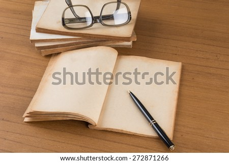 old book with pen on wood table - stock photo
