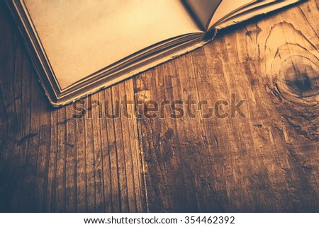 Old book wooden library desk, retro toned image, selective focus - stock photo