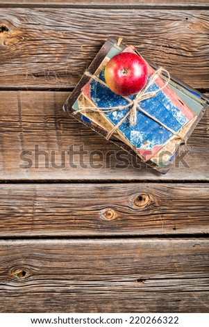 Old books and apple on school desk - stock photo