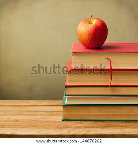 Old books and apple on wooden table over grunge background