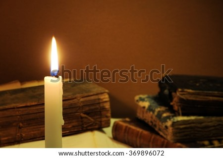 Old books and candle. Knowledge concept.