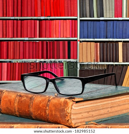 Old books and eye glasses in the library - stock photo
