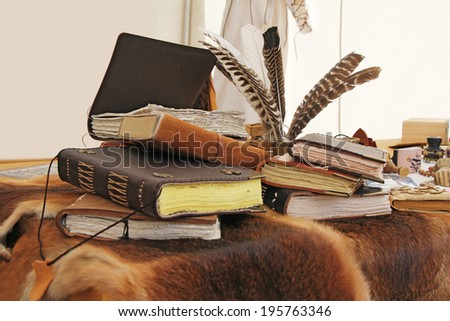Old books and inkstand on the fur leather