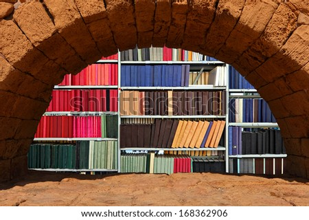 Old books and journals on bookcases in a window in a wall made of the Jerusalem stone - stock photo
