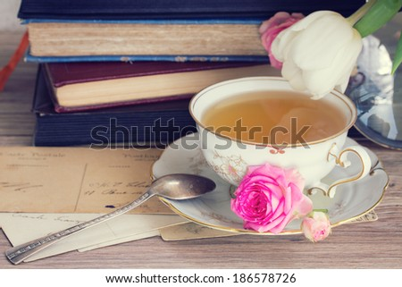 old books and mail with antique cup of tea - stock photo
