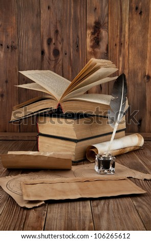 old books and pen on a wooden table - stock photo