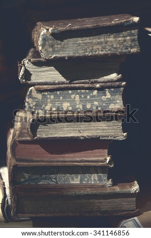 Old books for sale at flea market in Paris (France). A game of light and shadow. Selective focus. Toned dark photo. - stock photo