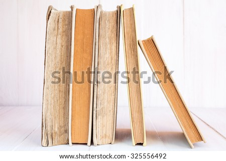 Old books in a row on wooden background - stock photo