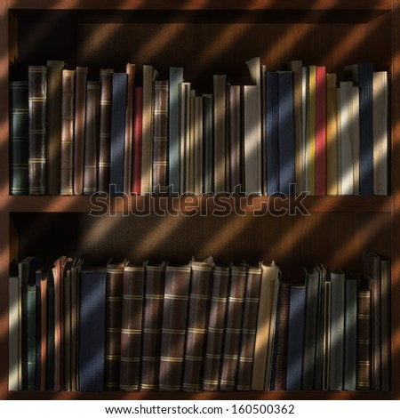Old books in library shelf with blinds shadow - stock photo