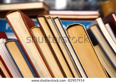 Old books leaning against each other for sale - stock photo