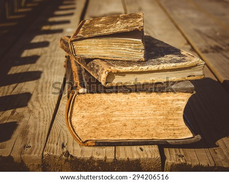 old books lie on a wooden table on the terrace in the sun - stock photo