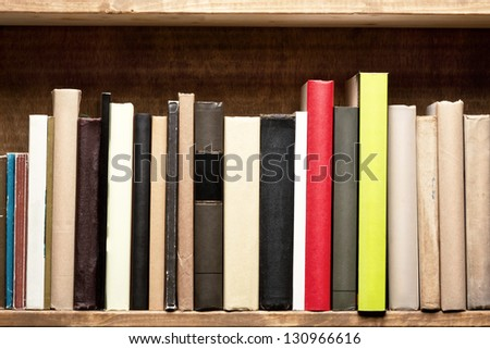 Old books on a wooden shelf. No labels, blank spine. - stock photo