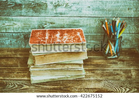 Old books on a wooden table against a wooden wall. Vintage and retro toning - stock photo