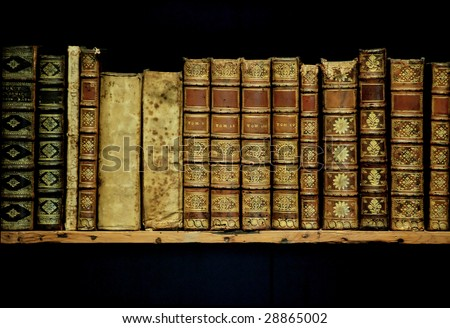 old books on an archival shelf of library of storehouse on  isolated black background