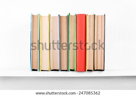 Old books on bookshelf on white wall background - stock photo