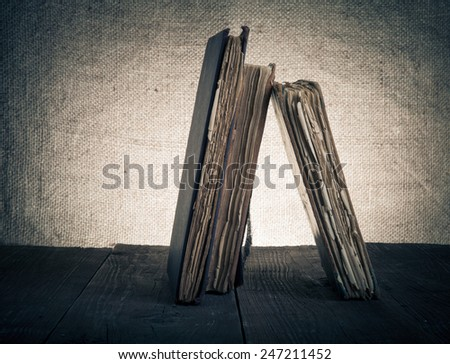Old books on old wooden table against the background of burlap. Toned. - stock photo