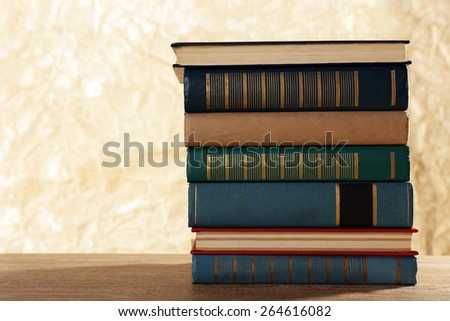 Old books on wooden table on brown background - stock photo