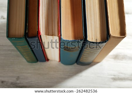 Old books on wooden table, top view - stock photo