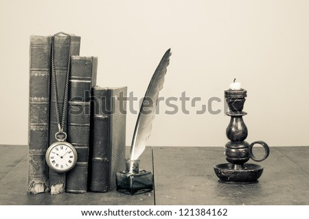 Old books, quill and inkwell, pocket watch, candlestick on wooden table - stock photo