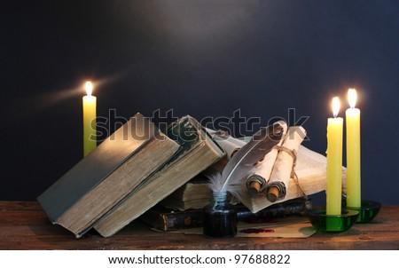 old books, scrolls, feather pen inkwell and candles on wooden table on blue background - stock photo
