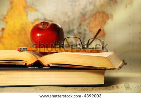 Old books with red apple and glasses on study desk - stock photo