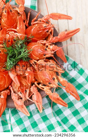 Old bowl with red boiled crawfish on a wooden table in rustic style, close-up, selective focus on some crawfishes. Place for text - stock photo