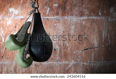 old boxing gloves and punching bag hang on hook on texture wall with copy space - stock photo
