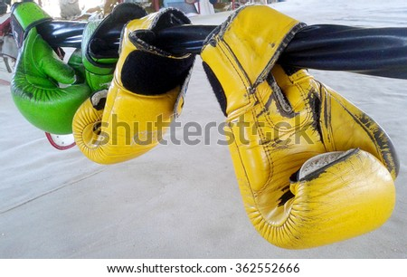 Old boxing gloves hangs off the boxing ring - stock photo