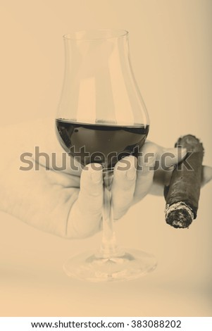 Old brandy or rum in glass and cigar in male hand on white background - stock photo