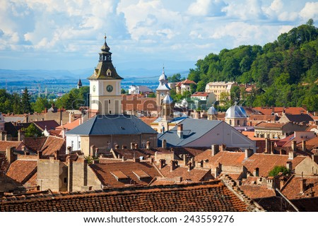 Old Brasov city buildings roof  and The Council House clock tower - stock photo