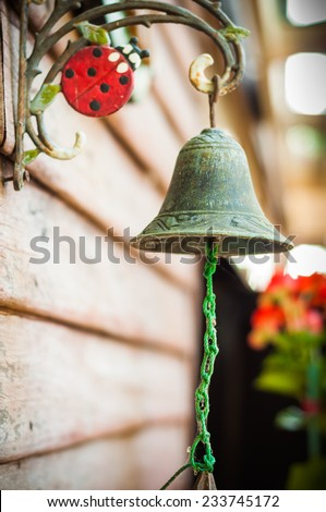 Old brass bell hang on house wall  - stock photo