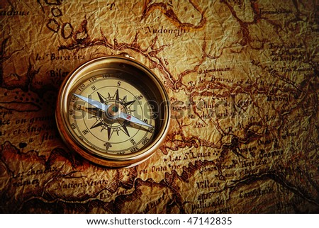 Old brass compass lying on a very old map - stock photo