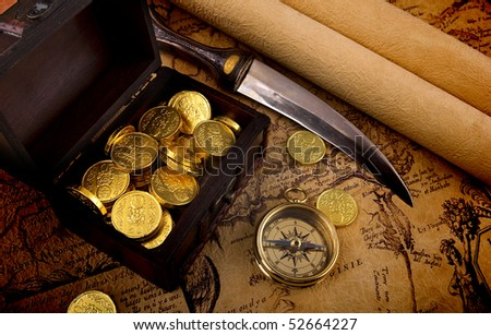 Old brass compass lying on a very old map with treasure chest full of golden coins - stock photo
