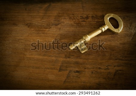 Old brass keys placed on a wooden floor low key light.