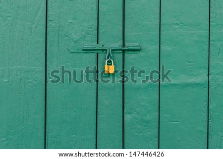 Old Brass Padlock on Wooden Green Gate