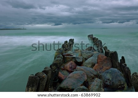 Old breakwater protecting the Baltic coast during a storm in a long exposure. - stock photo