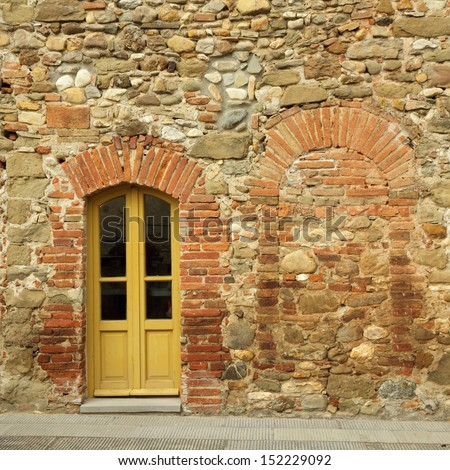 old brick and stone wall with door to the tuscan house, Anghiari, Italy - stock photo