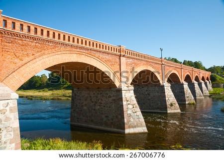Old brick bridge across the Venta river, Kuldiga, Latvia - stock photo