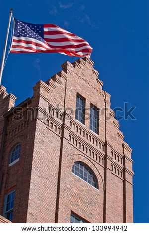 Old brick building, in a historic part of town, flying the American flag - stock photo