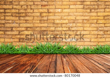 Old brick wall and green grass on wood floor - stock photo