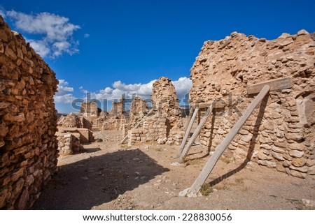 Old brick wall of historical city propped up by wooden props, in order to avoid not collapsed completely - stock photo