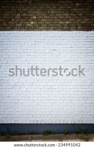 Old brick wall painted white and a side walk - stock photo