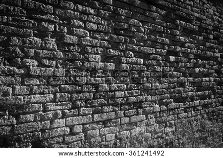 Old brick wall perspective (Venice, Italy). A game of light and shadow. Aged photo. Black and white. Vignette. - stock photo