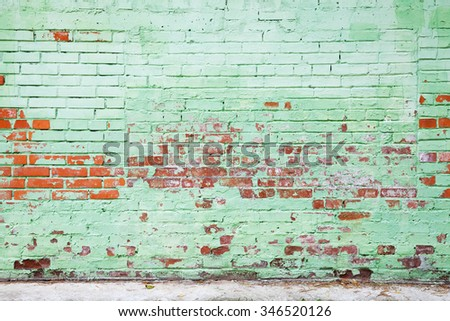 Old brick wall with damaged layer of green paint, background photo texture - stock photo