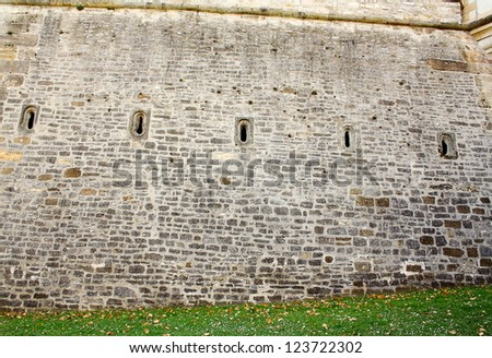Old brick wall with five loophole as background