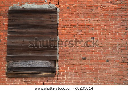 Old brick wall with weathered wood boarded window