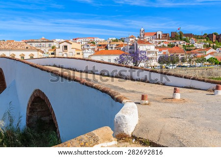 Old bridge in Silves town with view of famous castle and cathedral, Algarve region, Portugal - stock photo