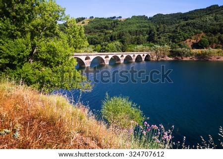 old bridge over lake in mountains of  Leon. Spain    - stock photo
