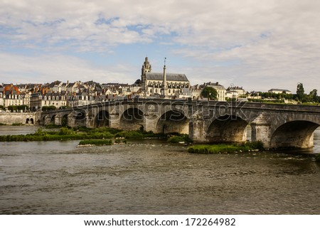 Old bridge over the Loire in Blois, France. Cathedral of Blois in the background - stock photo