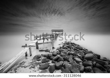 Old bridge to the sea (Black and White) - stock photo